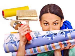 Builder woman with roll wallpaper. Isolated.